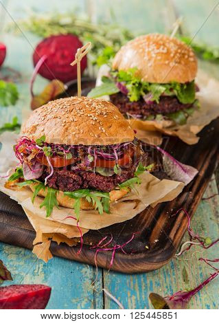 Close-up of home made vegetarian red beet burgers on wooden table.