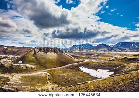 The magic of summer in Iceland. Unmelted snow in the valley among the yellow tundra