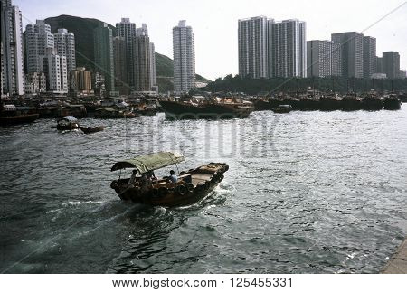 ABERDEEN / HONG KONG - CIRCA 1987: A wooden motorboat enters the harbor at the Aberdeen Floating Village in Hong Kong.