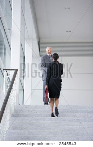 Man in suit smiling to a young woman climbing stairs