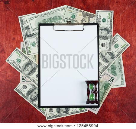 Blank paper sheet in clipboard placed on center of money dollar and wood background, sandglass, business concept and information mockup