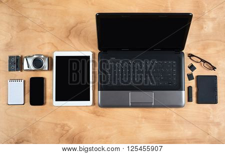 Flat lay of personal office accessories, laptop, notebook, coffee cup  and camera on wood background, top view