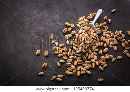 Pistachios over dark background. Food background with copyspace. Top view