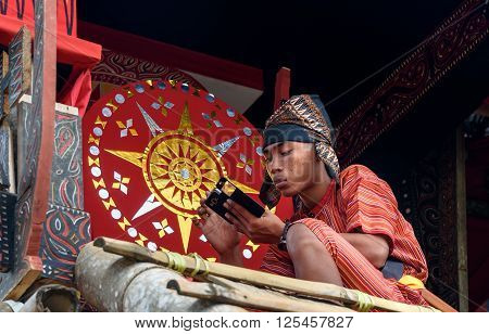 Boy In Traditional Clothes Near The Coffin At Funeral Ceremony. Tana Toraja