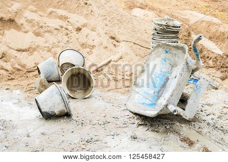 Blue sand barrow park lie on one side bucket and sand pile beside at a construction site.