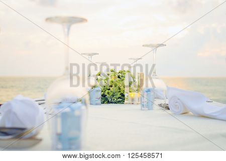 Romantic dinner setting on the beach at sunset.