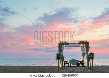 Romantic dinner setting on the beach at sunset. Copy sapce.