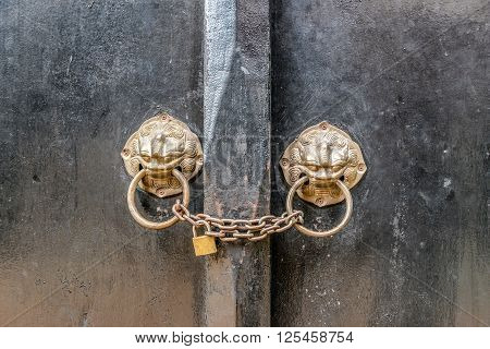 Ancient wooden gate with two door knocker rings
