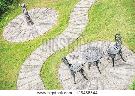 Vintage style garden design table set for two furniture stucco walkway and green grass.