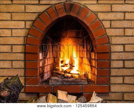 Open Fire In Indoor Brick Fireplace