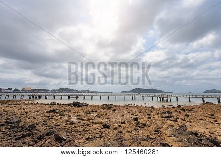 Dry beach and long bridge with cloudy sky in Suttahip of Chonburi Thailand.