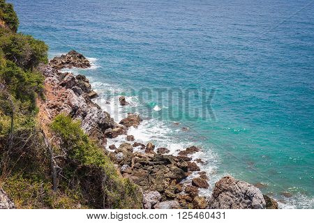 aerial view on rock coast with wave from deep blue sea in Kho Kham island in Suttahip of Chonburi Thailand