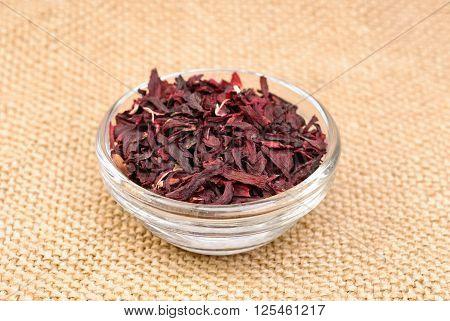 Hibiscus tea macro dry flower on glass bowl on canvas