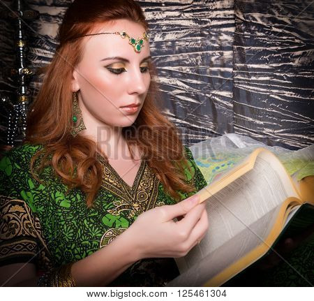 Closeup of Beautiful woman dressed in oriental style with oriental patterns on the hands and face, reading a thick book.