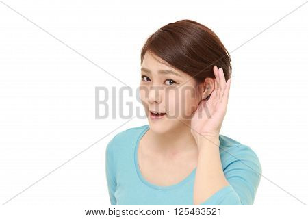 young woman with hand behind ear listening closely