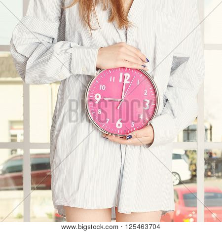 Young woman in striped shirt holding red alarm clock feeling pain or hunger in stomach
