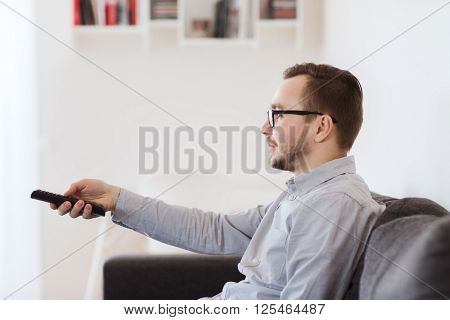 home, people, technology and entertainment concept - smiling man in eyeglasses with tv remote control at home