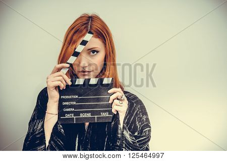 Pretty redheadn actress with movie clapper board looking at camera vintage color effect