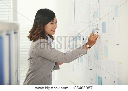 Project manager working with diagrams and blueprints in the office