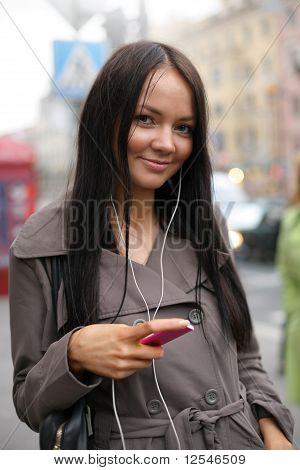 Young Woman With Music Player Walking In A Street