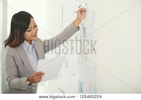 Project manager correcting blueprint according to document