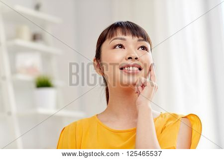 people, race, ethnicity and portrait concept - happy asian young dreaming woman or teenage girl face at home