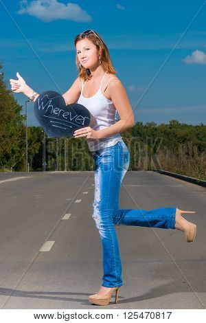 Woman In Jeans And T-shirt Of 30 Years Old Travels Hitchhiking