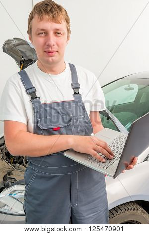 Engineer Of Mechanics With A Laptop Near A Car In A Garage