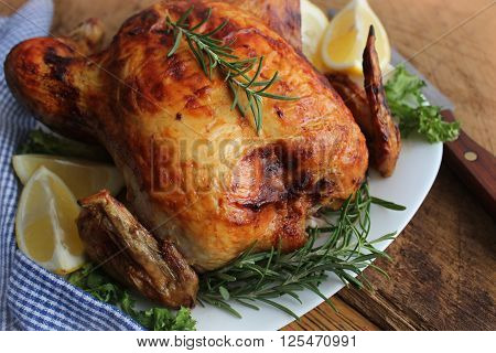 Whole roasted chicken with herbs on wooden table
