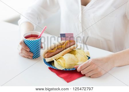 independence day, celebration, patriotism and holidays concept - close up of woman eating hot dog with american flag decoration and potato chips, drinking juice and celebrating 4th july at home party