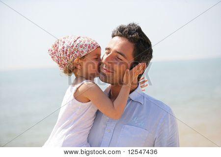 Porträt von einem kleinen Mädchen, die einen Mann auf die Wange küssen