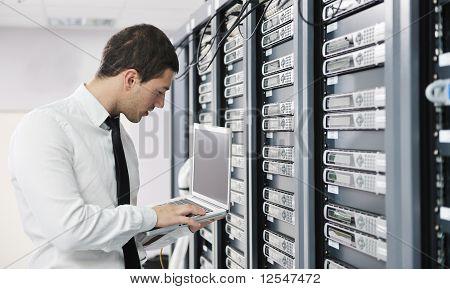 Empresario con el portátil en la sala de servidores de red