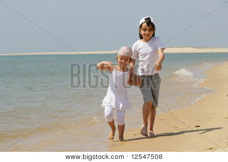 Niña y niño, dando un paseo por la orilla del mar