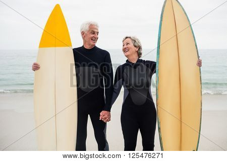 Senior couple with surfboard holding hand on the beach on a sunny day