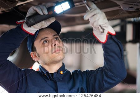 Mechanic using a light to inspect a lifted car