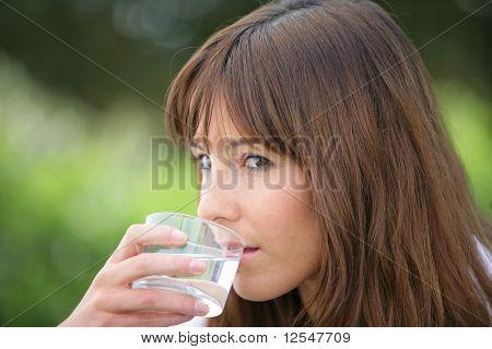 Retrato de una mujer joven con un vaso de agua
