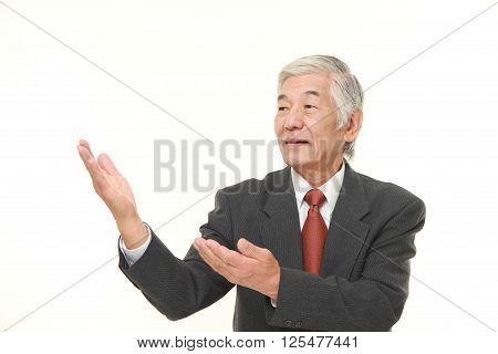 senior Japanese businessman presenting and showing something