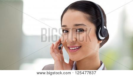 Close up of a smiling operator posing with a headset against steaming cup of coffee