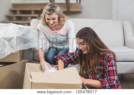 Friends unpacking carton boxes in their new house