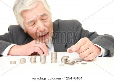 stack of coins  collapsed when businessman put a coin