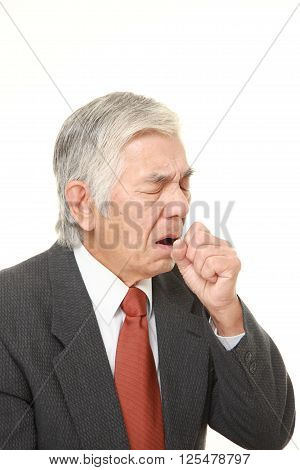 studio shot of senior Japanese businessman coughing