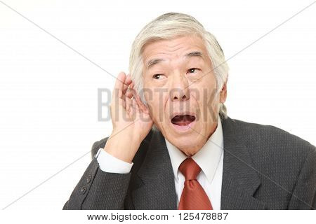 senior Japanese businessman with hand behind ear listening closely