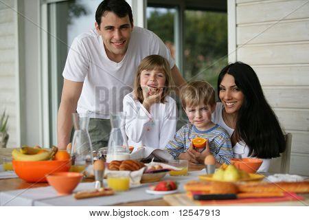 Portrait of a family having breakfast on a terrace