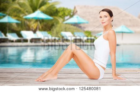 people, beauty and summer holidays concept - beautiful young woman in cotton underwear showing smooth skin of her legs over exotic hotel resort beach with swimming pool and sunbeds background