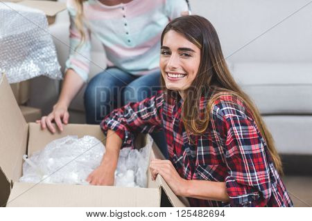 Portrait of woman unpacking carton boxes in their new house