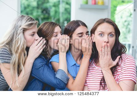 Women in a row whispering secrets in their friends ears at home