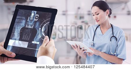Surgeon using digital tablet with group around table in hospital against biochemistry student using large microscope
