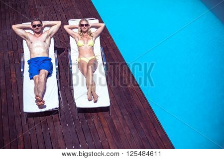 Couple relaxing on a sun lounger near the pool