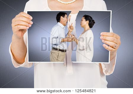 Woman holding a torn photo against grey vignette