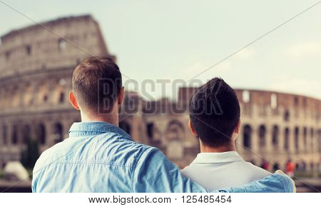 people, homosexuality, same-sex marriage, travel and love concept - close up of happy male gay couple hugging from back over coliseum in rome background